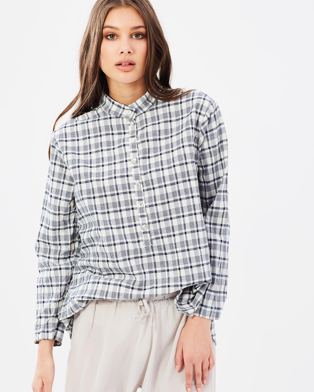 Photo of Primness Primness Check Pull On Tops Check Check Pull On - The Check Pull On by Primness is the classic boyfriend style cotton shirt. With a navy check print all over, a boxy over-sized fit and mandarin collar the pull on will be on high rotation in your wardrobe. - Length 82cm- Beige base with navy check pattern - Mandarin collar - Shell buttons - Low back hem - Half button up front - Made in Australia Material: 100% Woven Cotton