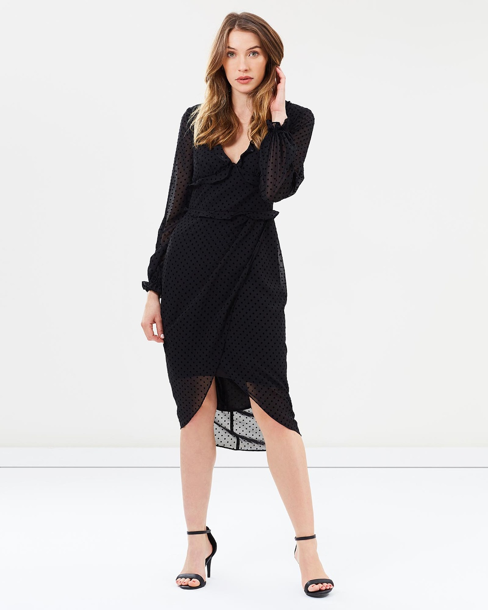 Photo of Cooper St Cooper St Harper Long Sleeve Drape Dress Dresses Black Harper Long Sleeve Drape Dress - Playfully demure, the Harper Long Sleeve Drape Dress by Cooper St features an alluring V-neckline detailed with on-trend frilling and figure-hugging silhouette. Expertly worked in sheer flocked spot chiffon, the midi-length cocktail number comes finished with a fixed wrap skirt and tulip high-low hemline. Our model is wearing a size AU 8 dress. She is 173cm (5&rsquo8&rdqu