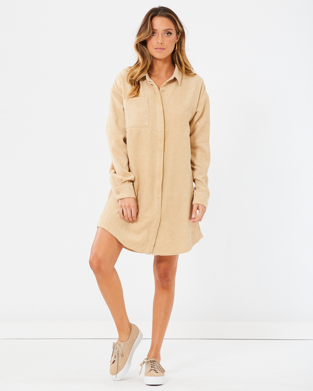 Photo of Calli Calli Brenda Dress Dresses Beige Brenda Dress - The Brenda Dress by CALLI, is the perfect piece to revive your wardrobe. Cut in a Corduroy fabrication, this dress features a shift silhouette, full-length sleeves, classic collared neckline, button up front and a functional pocket. This piece can easily be dressed up or down, simply add boots and a belt for a party look or sneakers for a daytime look. Our model is wearing a size AU 8 dress. S