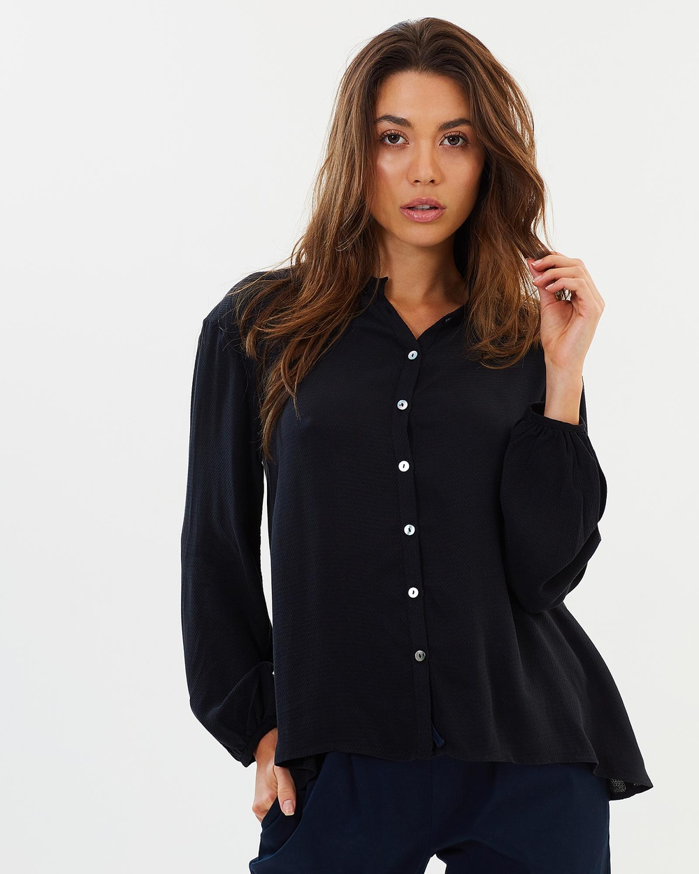 Photo of Privilege Privilege Ever After Swing Blouse Tops Black Ever After Swing Blouse - Striking the perfect balance between playful and professional, Privilege design flattering separates that boast fashion-forward flourishes that set them apart from the rest. Their Ever After Swing Blouse blends a traditional button-down with more whimsical details like blouson sleeves and relaxed, drapey silhouette. We love this blouse partially unbutton with a lace camisole peakin