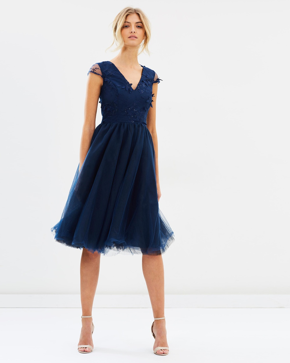 Photo of Chi Chi London Chi Chi London Cosette Dress Bridesmaid Dresses Navy Cosette Dress - Exuding a delicate elegance and femininity, the Cosette Dress from Chi Chi London is full of soft curves and dreamy floral accents. The dark navy dress features a classic v-neckline and back, and a full midi skirt that billows down to just below the knees. Our model is wearing a size UK 8 dress. She usually takes a standard AU 8/Small, is 5'11