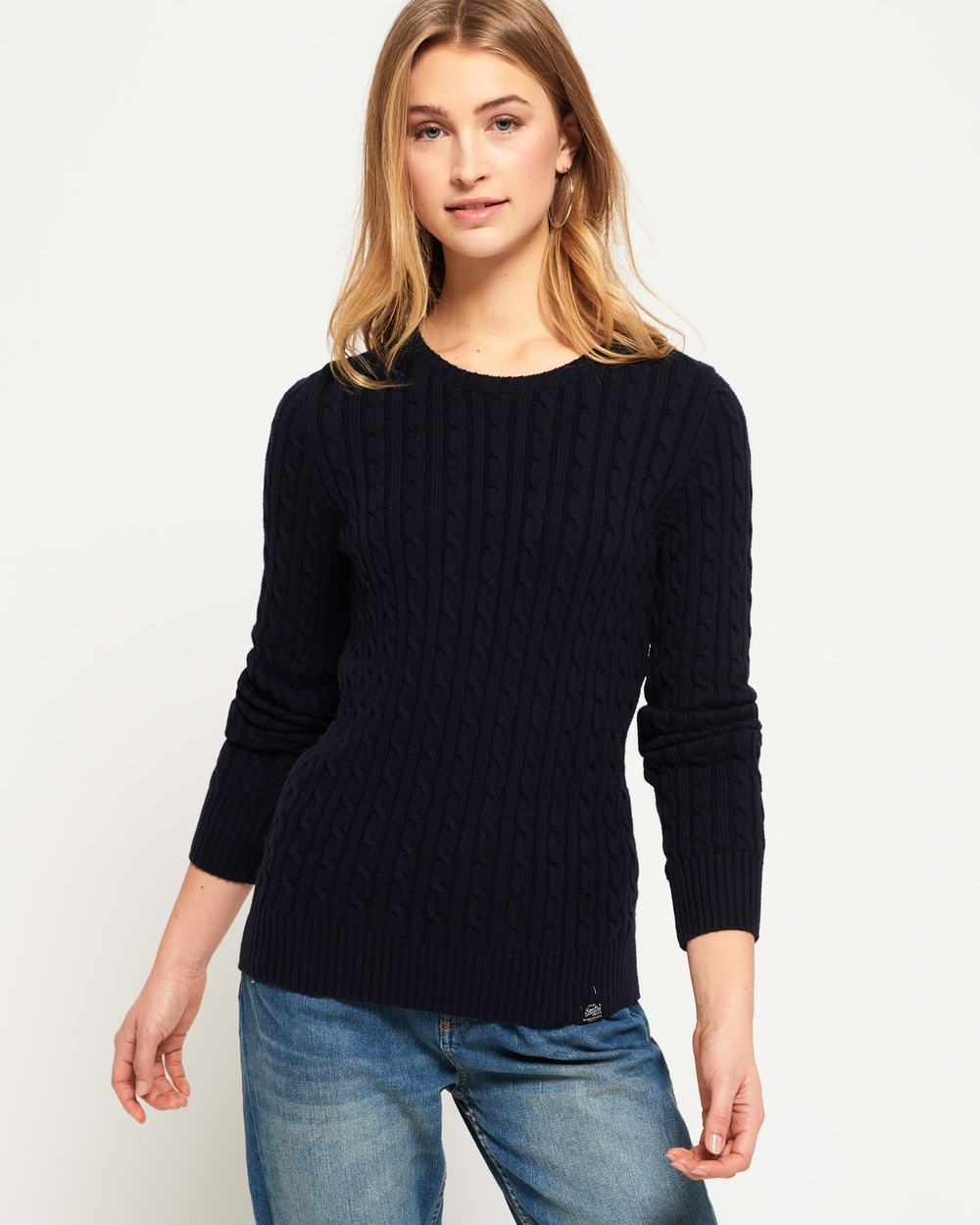 Photo of Superdry Superdry Croyde Cable Knit Jumper Tops Marina Navy Croyde Cable Knit Jumper - Superdry women's Croyde cable knit jumper. This cable knit jumper features a classic crew neck and ribbed hems and cuffs. This jumper is finished with a Vintage Superdry logo tab on the hem and a Superdry NYC logo badge on the sleeve. Model wears: 10/Small Model height: 5' 9